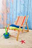 Beach chair. Chair and toys at the beach in front of blue background Royalty Free Stock Images
