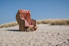 Beach chair. Traditional canopied beach chair at baltic sea with marram grass an blue sky in background Royalty Free Stock Photography