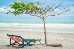 Beach chair and a tree. A beach chair, table and a tree on an empty beach Stock Photos