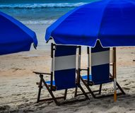 Beach chair, umbrella and ocean waves equal the best vacation. Relax on your beach chair with an umbrella and listen to the ocean waves crash on the shore stock photo