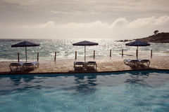 Beach chair with umbrella on private pool, ocean view Stock Photo