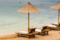 Beach chair and umbrella on sand beach. Concept for rest, relaxation, holidays, spa, resort Royalty Free Stock Image