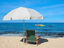 Beach chair with umbrella on the  shore Stock Photo