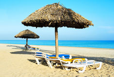 Beach chair under rustic umbrellas in the beach. Beach chair under rustic umbrellas in a deserted beach Royalty Free Stock Image