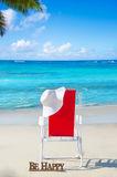 Beach chair with white hat by the ocean Royalty Free Stock Images