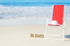 Beach chair with white hat by the ocean Stock Photo