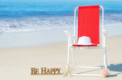 Beach chair with white hat by the ocean Royalty Free Stock Photography