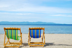 Beach chair on white sand beach with crystal clear sea Royalty Free Stock Images