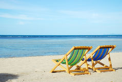 Beach chair on white sand beach with crystal clear sea Stock Image