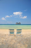 Beach chair on white sand beach with crystal clear sea Stock Photos