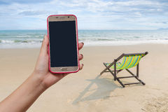 Beach chair on the white sand beach in summer with female hand holding smart phone mobile on pink case with black screen. Stock Image