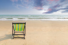 Beach chair on the white sand beach with sunset twilight sky and copy space. Summer background. Summer landscape concept. Romantic Stock Images