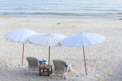 Beach chair and white umbrella parosol. Beach chair and white umbrella parosol on white sand beach with seaside background Stock Photos
