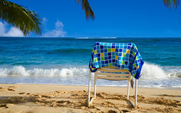 Beach chair. White beach chair under palm leaves by the ocean, with towel Stock Photo