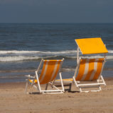 Beach chairs. Two beach chairs in the sand with the sea/ocean on the background, plenty of copyspace royalty free stock image