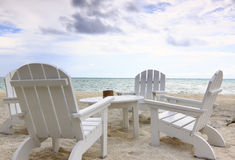 Beach chairs. A set of wooden beach chairs and a table on a sandy beach under cloudy sky stock photos