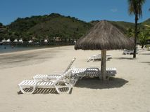 Beach chairs - 2. Inviting beach lounge chairs under thatched shades on a sunny white sandy beach stock photos