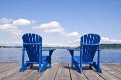 Beach chairs. Two blue chairs on a beach with beautiful view on a lake Royalty Free Stock Image