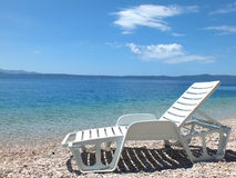 Beach chairs. White deck-chairs on the shore of the Mediterranean Sea, photography Stock Photo