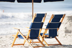 Beach chairs. Two luxury beach chairs sit under an umbrella on the sunny beach Royalty Free Stock Images