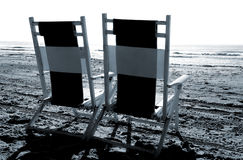 Beach chairs. Two beach chairs facing the waves royalty free stock image