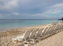 Beach Chairs. White beach chairs lined up along the Caribbean Sea Stock Photos
