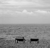 Beach chairs. Two unoccupied beach chairs, side by side on a rocky beach. Picture in monochrome Royalty Free Stock Images