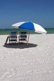 Beach chairs. Two beach chairs under an umbrella on a deserted beach Royalty Free Stock Photo