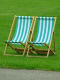 Beach chairs. Pair of beach chairs on grass stock photo