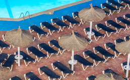 Beach chairs along a beautiful pool at night Royalty Free Stock Photography