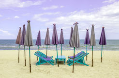 Beach chairs around with closed sun umbrellas on the white sand. Beach. Concept for rest, relaxation and holiday in Thailand Stock Image
