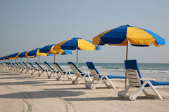 Beach chairs on the beach. Beach chairs and umbrellas are line up and waiting for sunbathers on a perfect day at the beach Royalty Free Stock Images