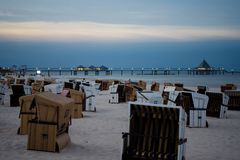 Beach Chairs on the beach in Germany Ostsee. Its noon and you see lights shining from the bridge Royalty Free Stock Images