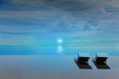 Beach chairs on the beach at night with moon rise, and dark blue environment Stock Image