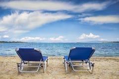 Beach chairs on the beach. Beach chairs on sand beach with cloudy blue sky royalty free stock photography