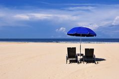 Beach chairs and blue umbrella Stock Photo