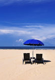 Beach chairs and blue umbrella Stock Photography
