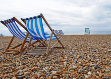 Beach Chairs on Brighton Beach. Beach in Brighton, England with a view of colourful deckchairs beachchairs on an overcast day. Empty pebble beach. End of summer Royalty Free Stock Photography