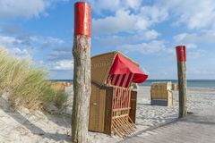 Beach chairs in Burgtiefe. Canopied wicker beach chairs on the South beach in Burgtiefe on the island Fehmarn at the Baltic Sea Stock Image