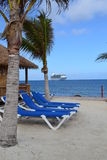 Beach chairs and cruise ship. Empty chairs near the ocean waiting for a couple to enjoy them Stock Photography