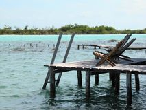Beach chairs in the dock. A dock with chairs in the Bacalar Lagoon Stock Image