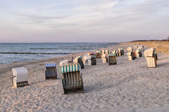 Beach chairs with dunes at sunset Stock Images