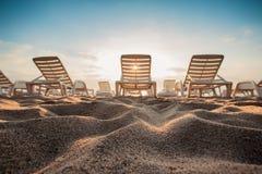 Beach chairs on the exotic tropical beach, sunrise shot Stock Photos