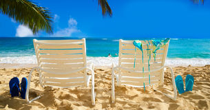 Beach chairs with flip flops by the ocean. Two white beach chairs under palm leaves by the ocean, with bikini and flip flops and couple in the ocean on Royalty Free Stock Photo
