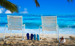 Beach chairs with flip flops by the ocean. Two white Beach chairs under palm leaves by the ocean, with flip flops and seashell with sunglasses Stock Images