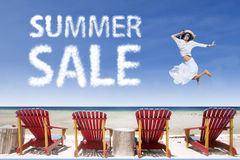 Beach chairs and girl jumping for summer sale stock image