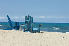 Beach Chairs Hawaii. Two empty blue Adirondack style chairs sit on a Hawaiian beach facing the Pacific ocean stock photos