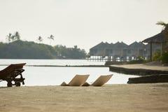 Two modern beach chairs on the beach. Indian ocean coastline on Maldives island. White sandy shore and calm sea. Travel. Beach chairs. Indian ocean coastline on stock photo