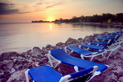 Beach chairs in Jamaica. Beach furniture at a Jamaican resort at sunset royalty free stock image