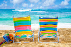 Beach chairs with kid's toys. Two colorful beach chairs under by the ocean with sunscreen and kid's beach toys, with couple in the ocean on background Royalty Free Stock Photos